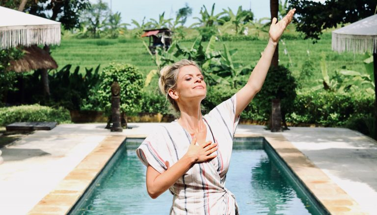 joanna hunt standing by pool holding one hand up and eyes closed