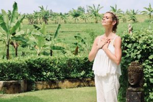 joanna hunt standing in green bali garden with her hands on her heart big image