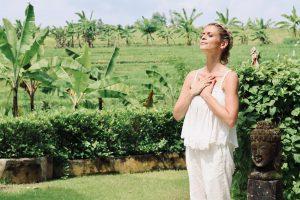 joanna hunt standing in green bali garden with her hands on her heart big image