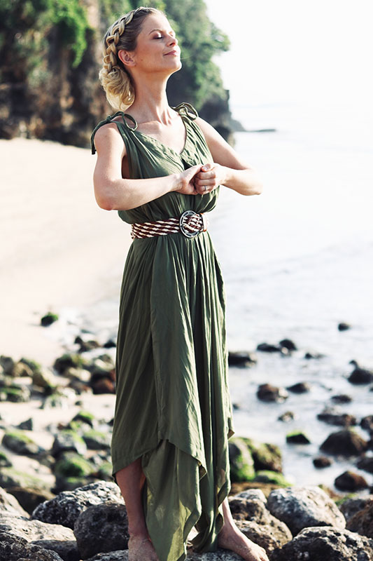 joanna hunt on beach in green dress standing holding hands and closing eyes