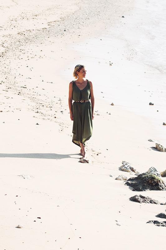 joanna hunt walking on white sand beach in green dress