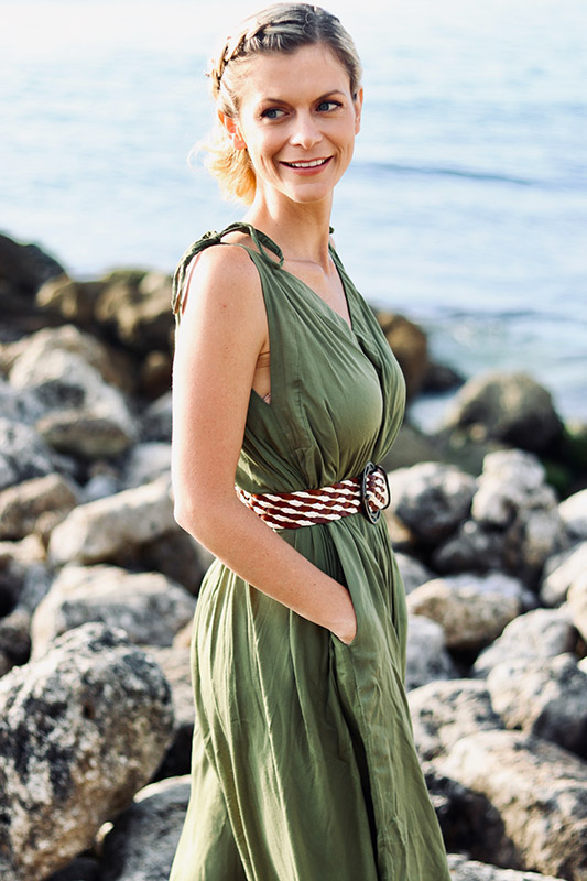 joanna hunt on beach in green dress standing with hands in her pockets and smiling