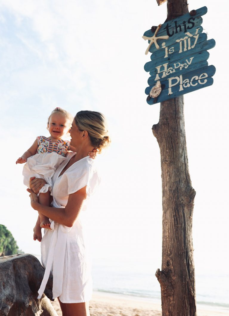 joanna hunt holding baby with this is my happy place sign on the beach