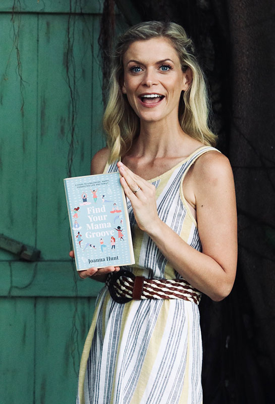 joanna hunt smiling holding her book find your mama groove