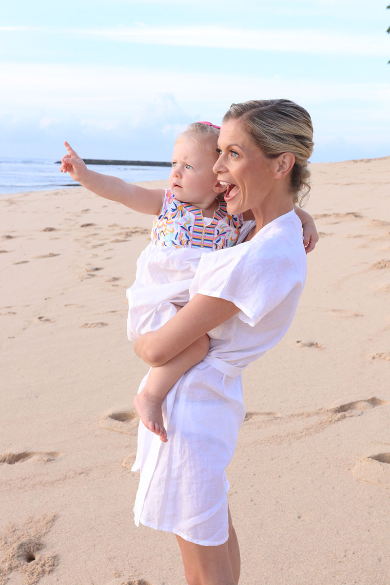 joanna hunt smiling on beach with daughter in arms