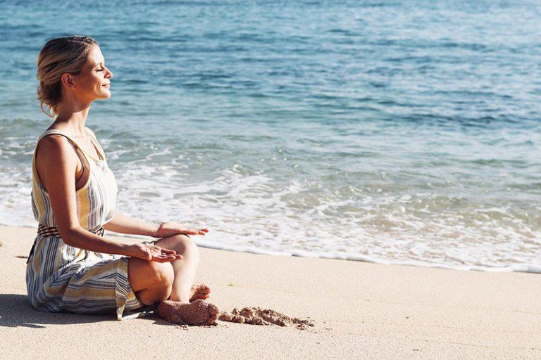 joanna hunt sitting on beach in yoga pose