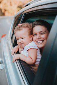mom and baby smiling out of car window